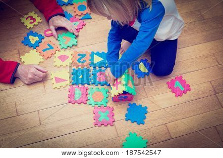 teacher and child playing with puzzle, early education