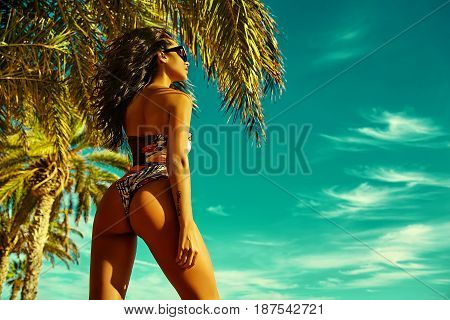 fashion outdoor photo of beautiful sexy hot woman model with dark hair in white colorful bikini posing on summer beach behind blue sky and palms in sunglasses