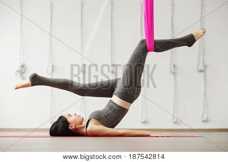 Aerial yoga exercise or antigravity yoga, woman stretching one leg, other fixed in hammock in sport studio or gym. Teenage girl building strength, enhancing flexibility, easing sore joints or muscles