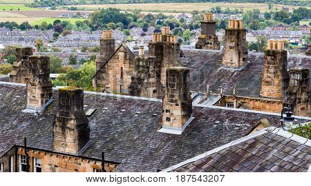 Close-up shot of old stone chimney stacks and wet slate canted roofs in Stirling Old Town Scotland.