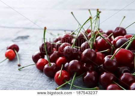 Cherry heap closeup on wood. Fruit background, healthy food