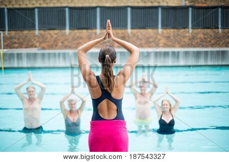 Rear view of yoga instructor assisting senior swimmers at poolside