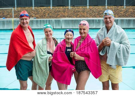 Portrait of happy senior swimmers covered in towels at poolside