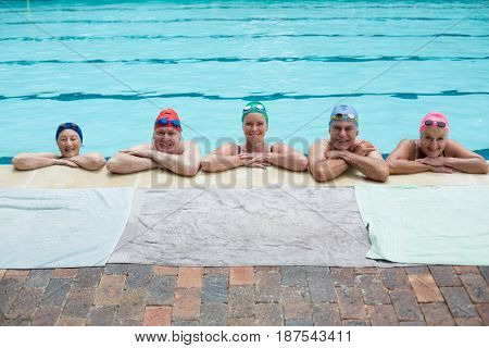 Portrait of senior swimmers leaning on poolside