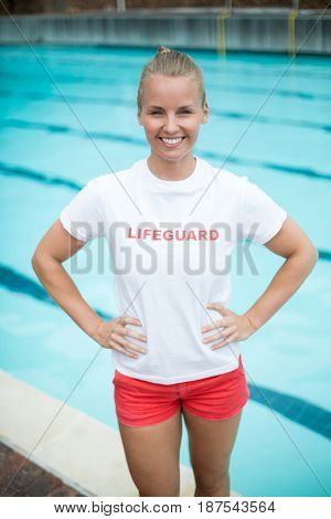 Portrait of confident female lifeguard standing at poolside
