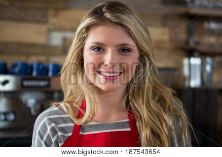 Close-up portrait of smiling young female barista in coffee shop
