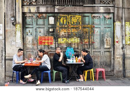 BANGKOK THAILAND- MAY 19 2017: Unidentified man eats on a street in chinatown district Bangkok Thailand. Chinatown is renowned for its street food and outdoor dining.