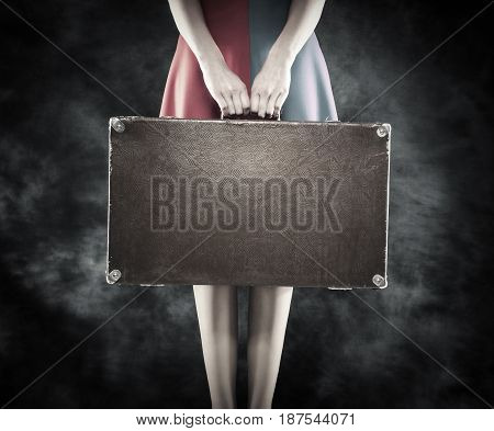Old suitcase in hands on a dark background.