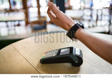Cropped image of man hand using smart watch to express pay in coffee shop