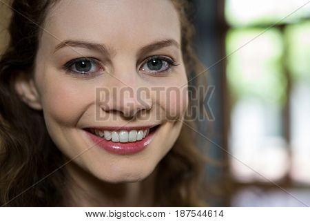 Portrait of beautiful young woman smiling in coffee shop