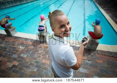 Portrait of female instructor monitoring children at poolside