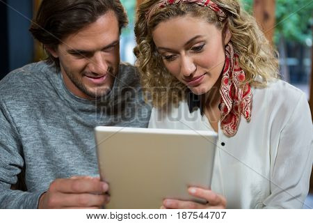 Young couple using digital tablet in coffee shop