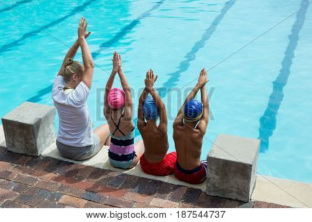 Rear view of female swimming instructor with students at pool side