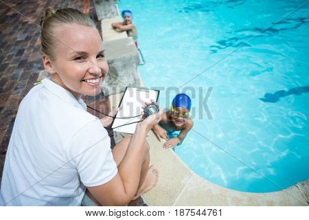 Portrait of female instructor monitoring time of children swimming in pool