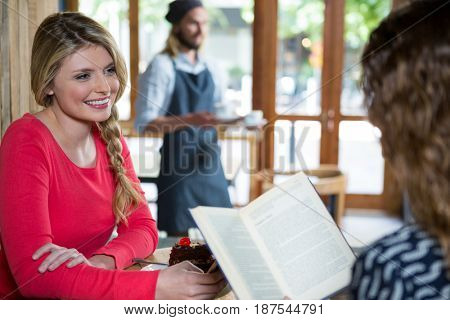 Smiling young woman looking at female friend in coffee shop