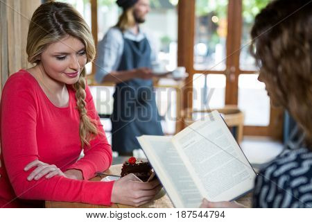 Young woman using phone while friend reading book in coffee shop