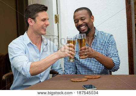 Cheerful male friends toasting beer glasses at restaurant table