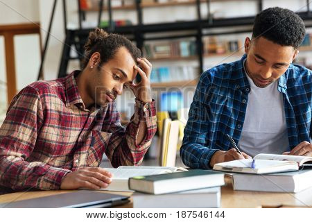 Picture of young two men students sitting in library reading books. Looking aside.