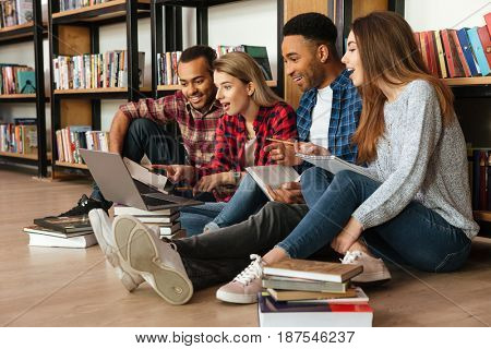 Image of young concentrated students sitting in library on floor using laptop computer. Looking aside.