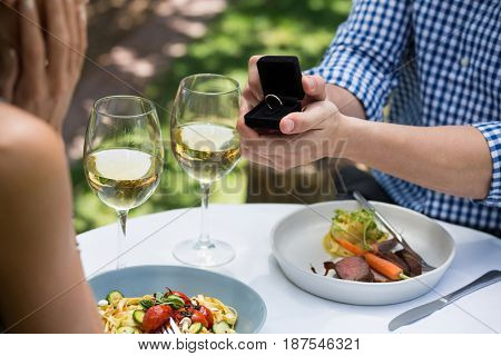Cropped image of man showing engagement ring to woman at outdoor restaurant