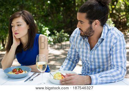 Young man looking at upset woman at outdoor restaurant