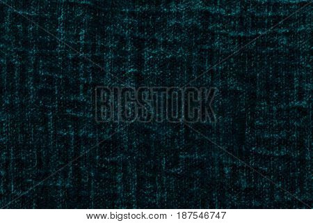 Dark green fluffy background of soft fleecy cloth. Texture of cyan plush furry textile closeup.