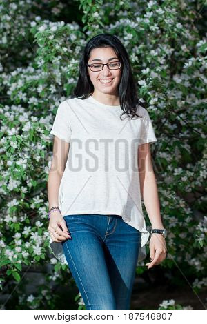 Girl in white t-shirt posing against a background of flowering bushes
