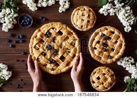 Homemade apple pie pies ready to eat hold female hands on dark wooden table with flowers, blueberry and apples. Traditional dessert on Independence Day. Food flat lay background