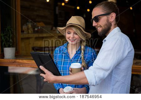Smiling young couple using digital tablet in coffee shop