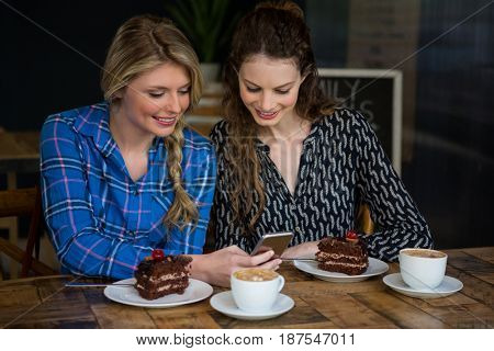 Beautiful young women using smart phone with dessert and coffee cups on table in cafe