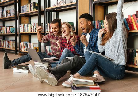 Picture of young happy students sitting in library on floor using laptop computer. Looking aside make winner gesture.