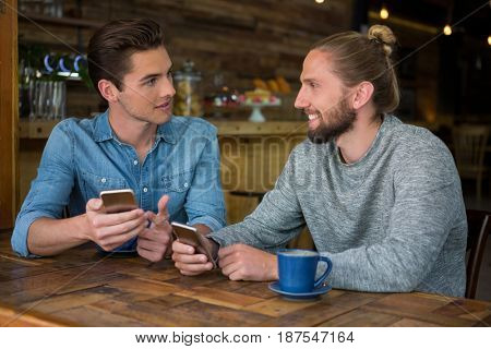 Young man talking with friend at table in coffee shop