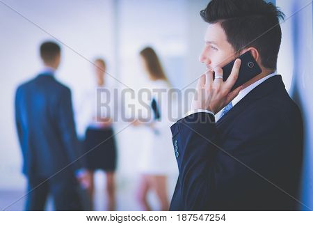 Businessman using mobile phone while leaning on wall in office