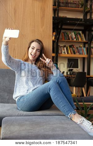 Image of young smiling woman student sitting in library make selfie with peace gesture by mobile phone. Looking aside.