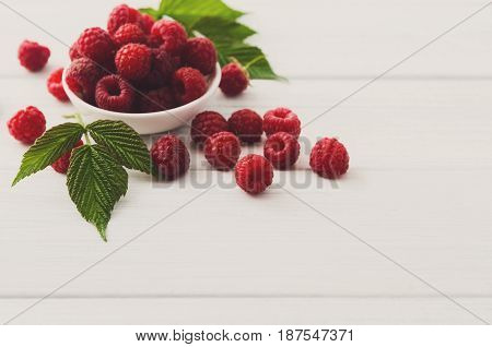 Red fresh raspberries on white rustic wood background with copy space