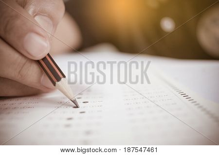 students hand holding pencil fill in Exam carbon test paper sheet and writing doing examination education in university college
