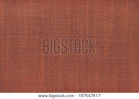 Dark orange background with chess pattern closeup. Structure of the brown fabric with checkerboard pattern macro.