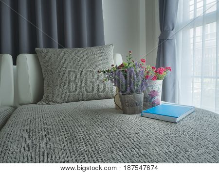 modern vintage sofa with variety colorful flower on pot and notebook paper blue cover on blurry beautiful white drape window texture background at bedroom.