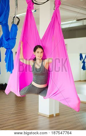 Young woman making antigravity yoga exercises with pink hammock in sport gym. Girl sitting on longitudinal splits in air, aerial yoga concept