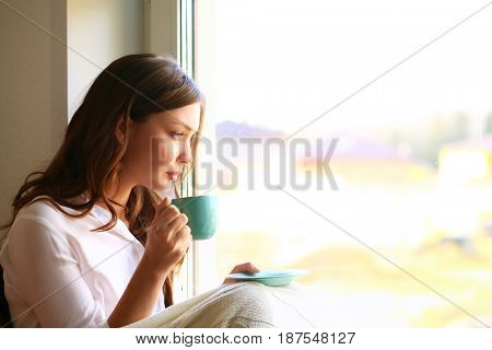 Young woman at home sitting near window relaxing in her living room reading book and drinking coffee or tea