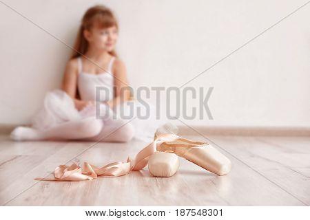 Ballet shoes and beautiful little ballerina in light dance studio