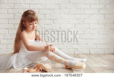 Beautiful little ballet dancer tying pointe shoes in light dance studio