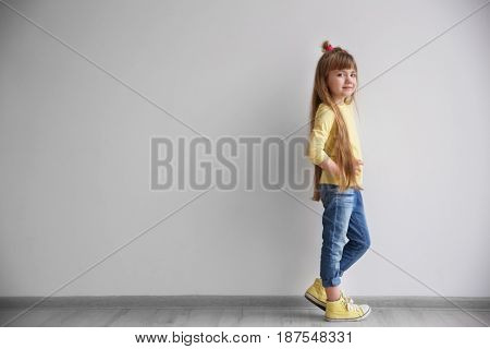 Little fashion girl standing in light room