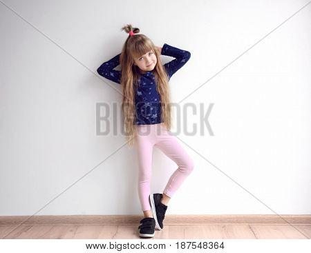 Little fashion girl posing in light room