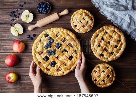 Homemade organic apple pies hold female hands on dark wooden kitchen table with raising, bluberry, rolling pin and apples. Traditional dessert on Independence Day. Flat lay bakery food background.