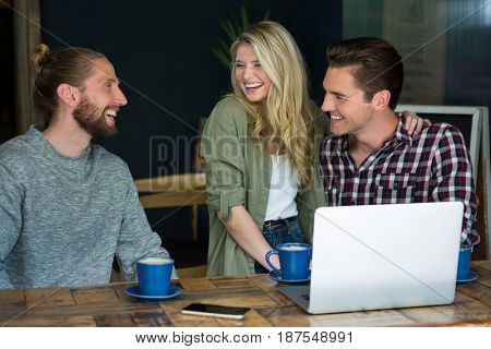 Cheerful young male and female friends talking in coffee shop