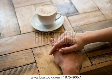 Cropped image of couple holding hands with coffee cup on table in cafe