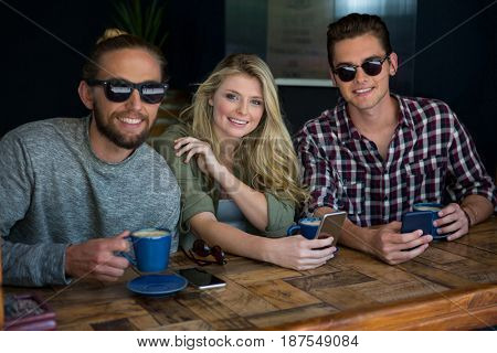 Portrait of woman with male friends wearing sunglasses in coffee shop