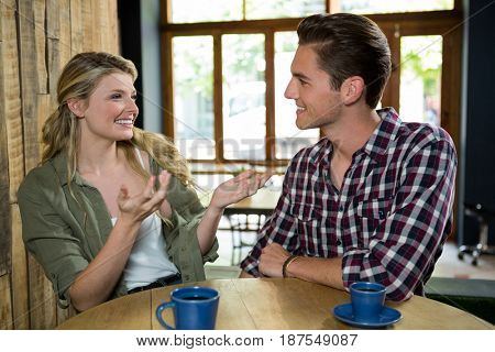 Happy young woman talking with man at table in coffee shop
