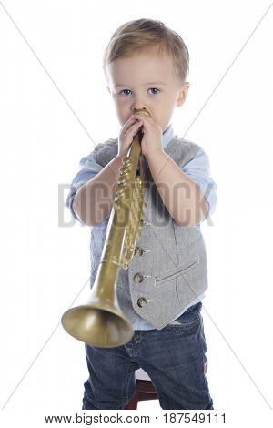 An adorable preschooler looking at the viewer as he blows a toy trumpet.  On a white background.
